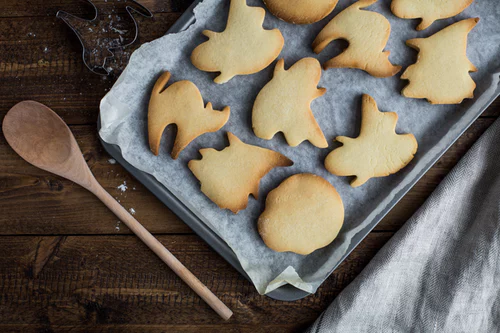 Best fall treats - Halloween cookies on parchment paper on a baking sheet. A wooden spoon lays next to the baking sheet.